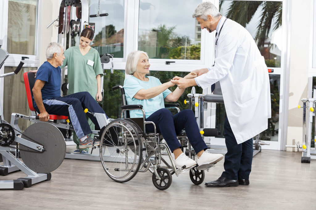 Photo of Doctor Holding Senior Woman's Hands In Wheelchair