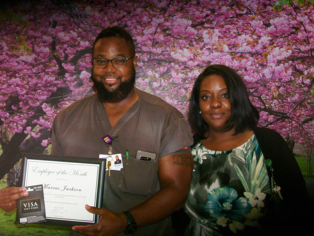 Marcus Jackson posing with Employee of the Month award with female.