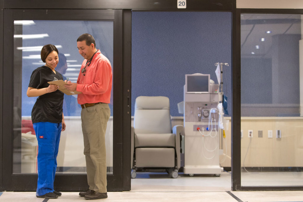 Staff discuss chart in front of dialysis room