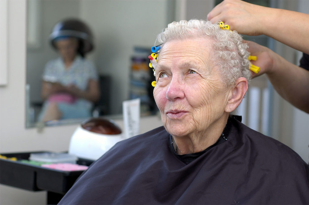Happy senior woman getting her hair curled at a beauty salon
