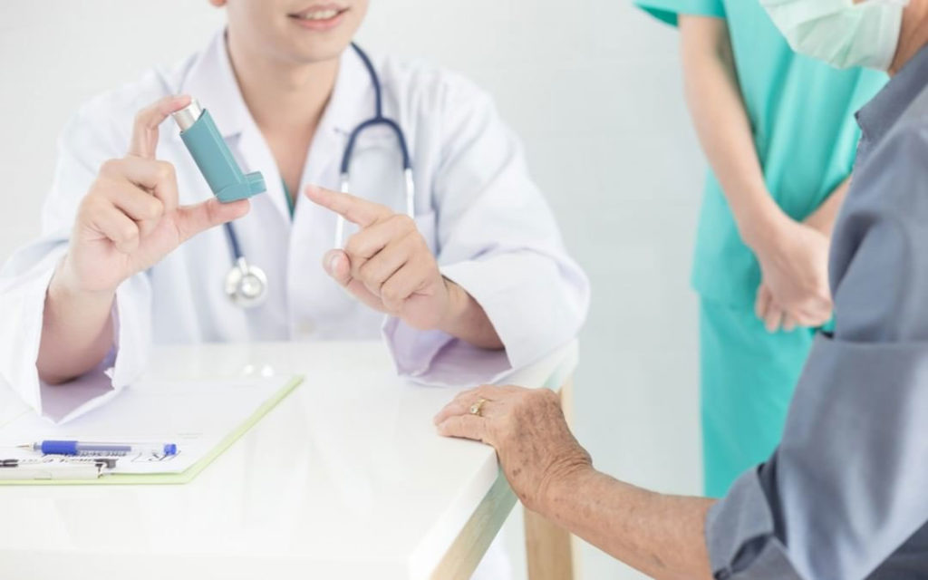doctor explains how to use inhaler medicine, asthma clinic, elderly disease, he's holding inhaler medicine with hand